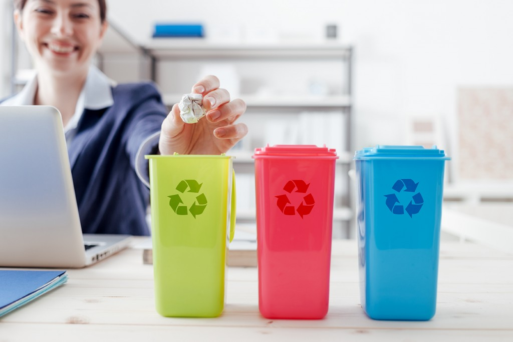 office employee practicing waste management by recycling